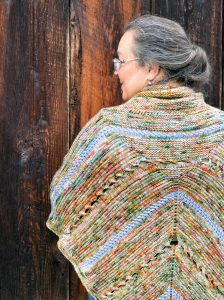 The pattern designer wearing the Bonfire Poncho shown from the rear with her face turned to the left